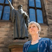 Dr Jane Dawson FRSE John Laing Professor of Reformation History. Photographed with the statue of John Knox in the Quad at the School of Divinity, Edinburgh.